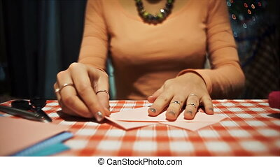 Female making origami from pink paper for valentines day