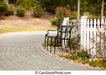 Iron Park Bench near a White Picket Fence in a Rural...
