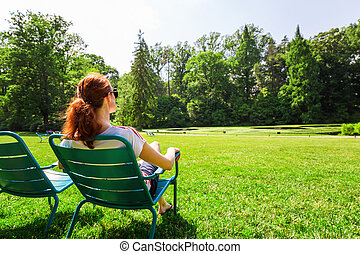 Woman in eyeglasses relax on greenfield. - Young woman in...