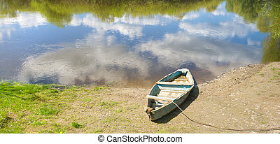 summer landscape. Wooden boat on the river bank.wooden boat...