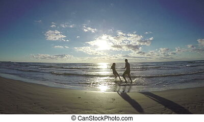 Couple silhouette teasing one another on a wet sandy beach