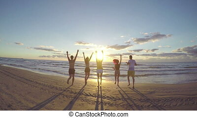 Group of friends running towards the sea on a beautiful beach at sunrise