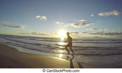 Handsome young man running on wet sandy beach