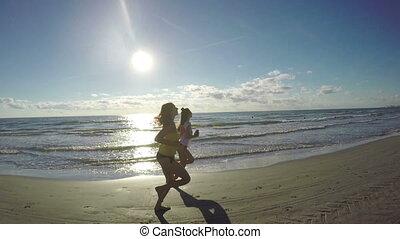 Girlfriends jogging along the beach