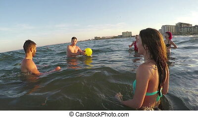 Friends having fun and playing volleyball in the sea