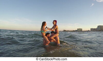 Couples playing in the sea - guys carrying their girls on their shoulders