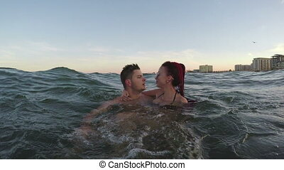 Two couples in love in the sea - man and woman kissing with...