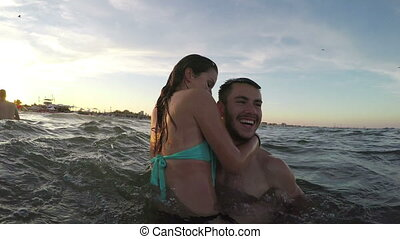 Couples having fun in the sea - guys carrying girls in their...