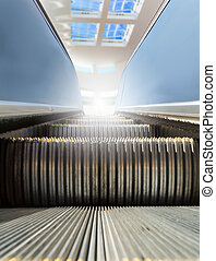 Modern escalator with window at the background. - Modern...