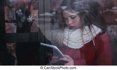 Chubby girl with tablet pc through the window - Young girl...