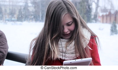Young girl sitting at bus stop and watching tablet pc -...