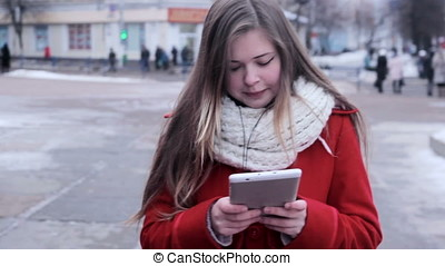 Moon-faced girl walks at street and watching tablet pc