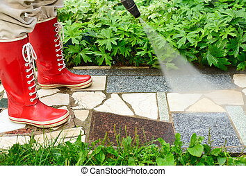 High pressure washing - Person in red gumboots cleaning...