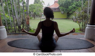 Rainy day on the island of Bali. The girl meditates in a...