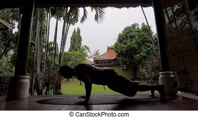 Silhouette of young fit man having training of trunk curl on...