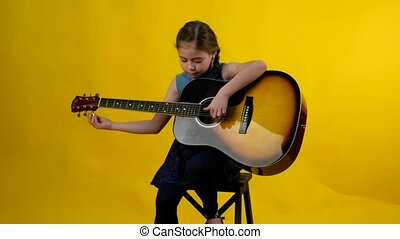 BLONDE GIRL BLUE EYES PLAYS GUITAR - young girl with a...