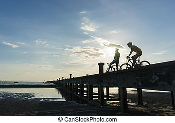 Silhouettes of cyclists with bicycles on the bridge