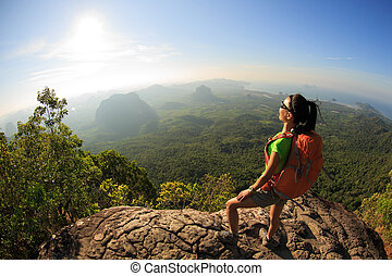 young traveler with backpack on the mountain peak rock...