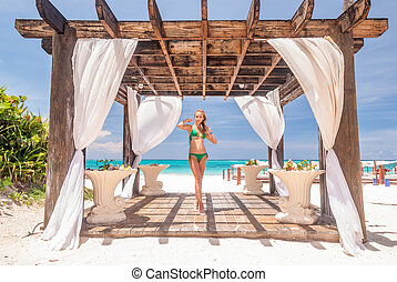 Woman at caribbean beach with pergola (gazebo) in Dominican...