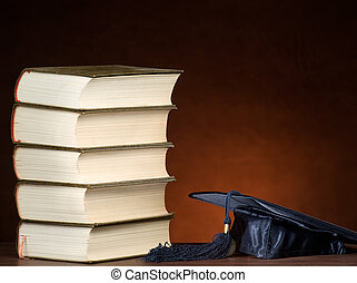 Stack of books and graduation cap