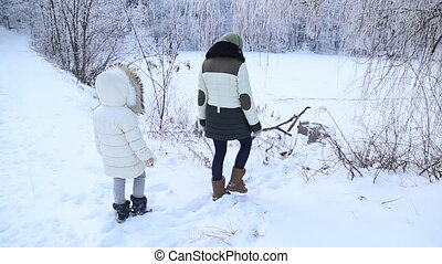 Mom and daughter walking through the woods