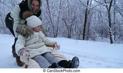 Mom daughter rolls on a sled in the winter forest