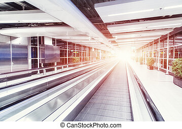 Moving waklway in the airport terminal. Backlight - Moving...