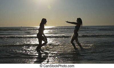 Two beautiful teenage girls playing and hugging in the sea...