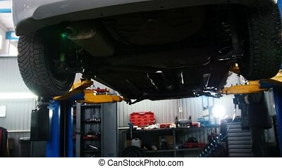 Automobile car diagnostic - mechanic working under a lifted...