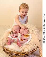 Toddler boy with identical twin babies - Toddler boy posing...