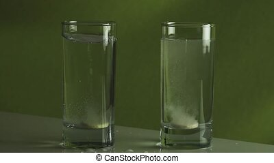 Tablet dissolves in glass of water slow motion stock footage...