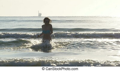 Young woman running in the waves of the sea towards the shore