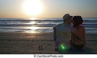 Couple kissing on sandy beach at beautiful sunrise