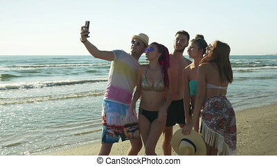 Five friends taking selfie on sandy beach