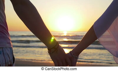 Romantic couple holding hands and walking towards the water on sandy beach
