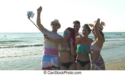 Friends on the beach having taking photos with a selfie stick