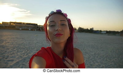Beautiful young woman taking a selfie on beach at sunset