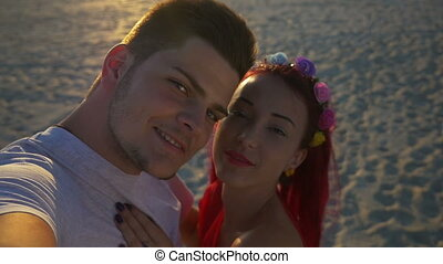 Beautiful lovers on video calling their friends from beach at sunset