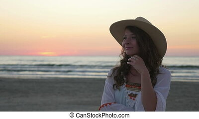 Woman with hat posing on the beach at sunrise