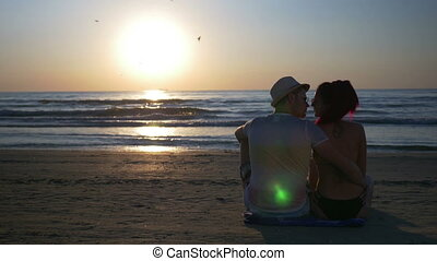Romantic lovers on the beach hugging and kissing at twilight...
