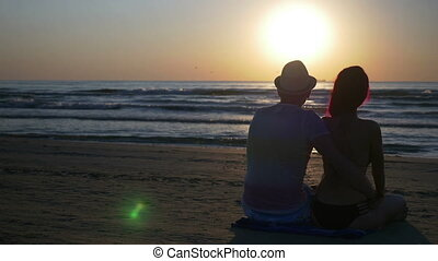 Romantic couple sitting on the beach hugging and kissing at sunrise