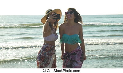 Two girlfriends taking selfie on the beach and getting...