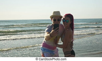 Beautiful lovers taking selfie on the beach and looking at photos