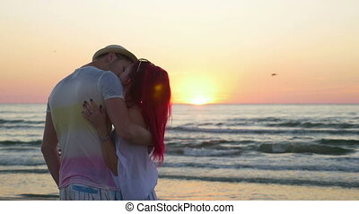 Young beautiful couple kissing at twilight on the beach