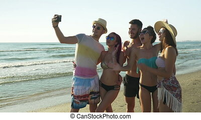 Group of friends taking selfie on the beach