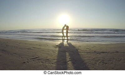 Couple silhouette playing in the sea and kissing on the beach at sunrise