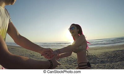 Young couple holding hands and running on beach towards the...