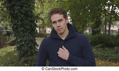 Young man looks at the camera with confidence in a park