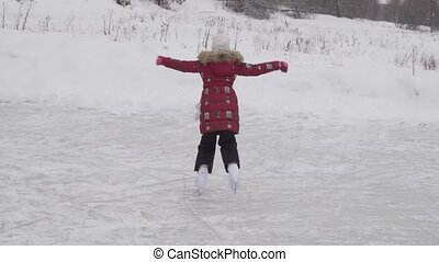 Beautiful young girl riding on figure skates at outdoor rink