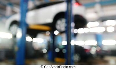 Automobile service - mechanics checking lifted car,...